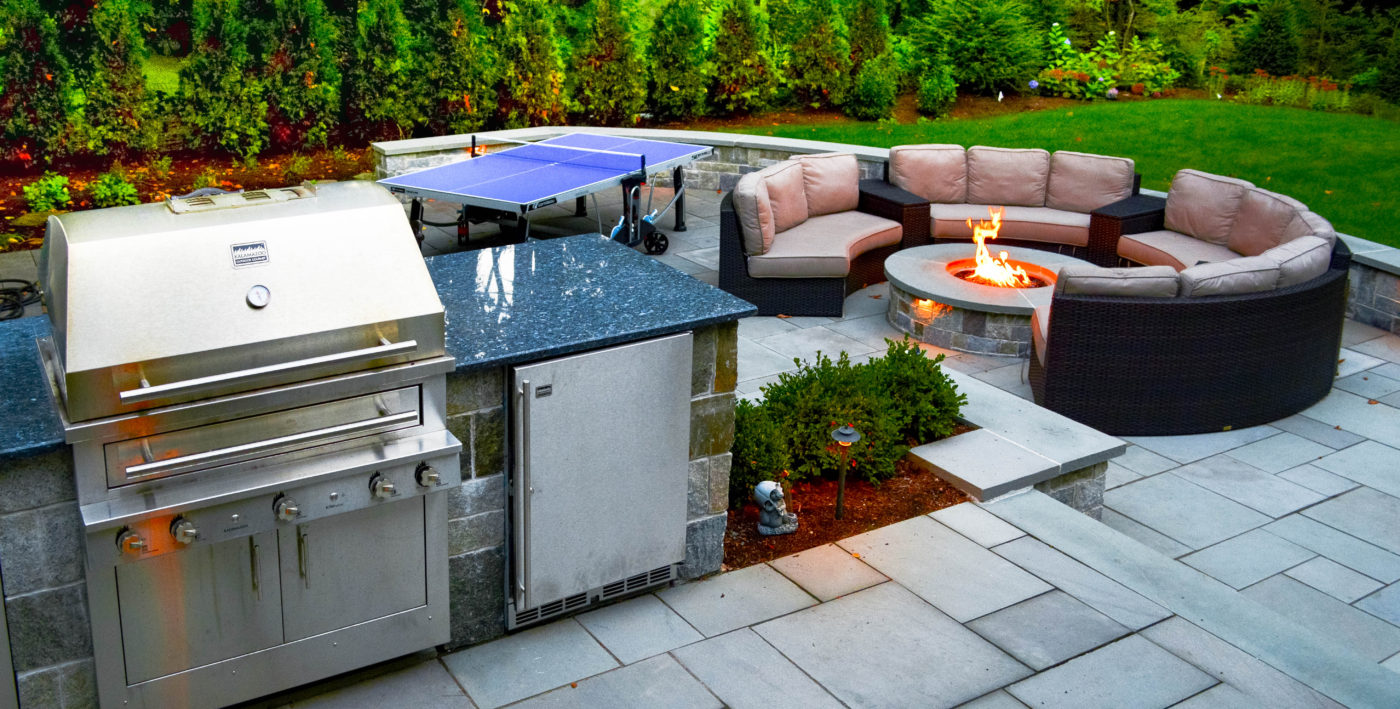 paved stone backyard with grill island and fire pit